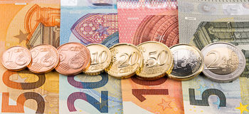 Fila de las monedas del centavo euro en billetes de banco Imagenes de archivo