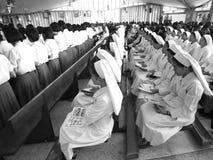 Fila de las monjas que se sientan tranquilamente en iglesia Fotografía de archivo
