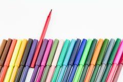 Fila de las plumas coloridas del color con una pluma diferente de la otra Imagen de archivo libre de regalías