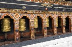 Fila de las ruedas de rezo en Tashichho Dzong, Timbu, Bhután Imagen de archivo libre de regalías