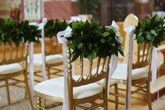 Fila de las sillas adornadas con las hojas del verde y las cintas blancas para la ceremonia de boda Fotos de archivo libres de regalías