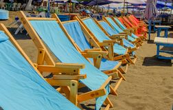 Fila de las sillas de cubierta en una playa caliente soleada Fotos de archivo libres de regalías