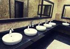 Fila de lavabos con los espejos en un retrete público fotos de archivo libres de regalías