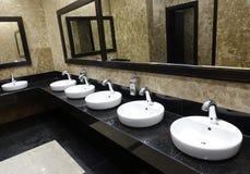 Fila de lavabos con los espejos en un retrete público imagen de archivo