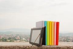 Fila de libros coloridos con el programa de lectura del e-libro Fotos de archivo