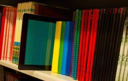 Fila de libros coloridos y del programa de lectura electrónico del libro imagen de archivo libre de regalías