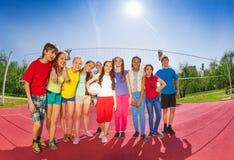 Fila de los adolescentes que se colocan en corte de voleibol Fotos de archivo