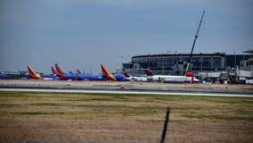 Fila de los aeroplanos del sudoeste y de Delta Airlines parqueados en sus puertas imagen de archivo