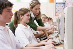 Fila de los alumnos que estudian adentro en los ordenadores Fotografía de archivo libre de regalías
