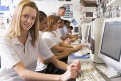 Fila de los alumnos que estudian en los ordenadores Imágenes de archivo libres de regalías