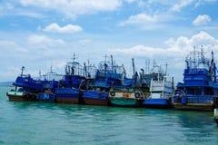 Fila de los barcos de pesca azules en el embarcadero Fotos de archivo
