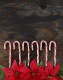 Fila de los bastones de caramelo en el fondo de madera Imagen de archivo libre de regalías