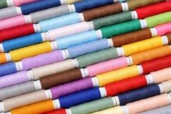 Fila de los carretes coloridos del hilo Imagenes de archivo