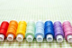 Fila de los carretes del hilo en colores del arco iris fotografía de archivo