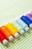 Fila de los carretes del hilo en colores del arco iris foto de archivo