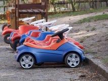 Fila de los coches coloridos del juguete para los niños en un patio Fotos de archivo libres de regalías