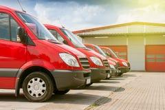 Fila de los coches rojos de la entrega y del servicio Foto de archivo