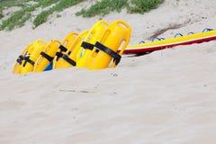 Fila de los dispositivos de flotación amarillos brillantes en la playa imagenes de archivo