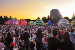 Fila de los globos parcialmente inflados del aire caliente que suben contra el cielo de la puesta del sol imagen de archivo libre de regalías
