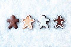 Fila de los hombres de pan de jengibre en nieve Foto de archivo libre de regalías