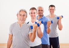 Fila de los hombres que trabajan con pesas de gimnasia Fotografía de archivo libre de regalías