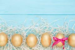 Fila de los huevos de Pascua de oro en fondo de madera azul Foto de archivo