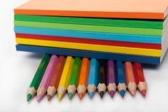 fila de los lápices bajo la pila de libros Imagen de archivo libre de regalías