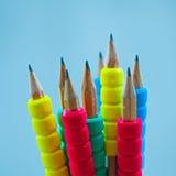 Fila de los lápices del color en fondo azul estudio Imagenes de archivo
