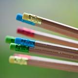 Fila de los lápices del color en fondo verde Arte Fotos de archivo