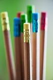 Fila de los lápices del color en fondo verde Arte Imagen de archivo