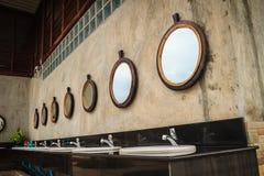 Fila de los lavabos blancos en el cuarto de baño con la fila de espejos adentro fotos de archivo