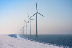 Fila de los molinoes de viento holandeses que desaparecen en calina del invierno imagen de archivo libre de regalías