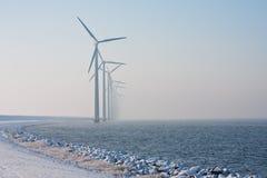 Fila de los molinoes de viento holandeses que desaparecen en calina del invierno fotografía de archivo libre de regalías