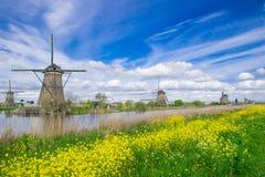 Fila de los molinos de viento tradicionales a lo largo del canal azul en Kinderdijk, Holanda Fotos de archivo
