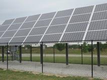 Fila de los paneles solares debajo de un cielo nublado Imagen de archivo