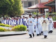 Fila de los sacerdotes que caminan en iglesia Imágenes de archivo libres de regalías