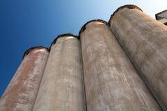 Fila de los silos de grano debajo del cielo azul Foto de archivo libre de regalías