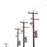 Fila de los transformadores del polo de poder aislados en blanco Fotos de archivo libres de regalías