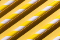 Fila de los tubos coloridos, rayas en el fondo amarillo plano foto de archivo libre de regalías