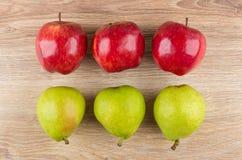 Fila de manzanas rojas y de peras verdes en la tabla de madera Imagen de archivo libre de regalías