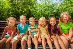 Fila de niños en el banco en parque Foto de archivo