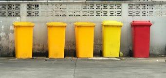 Fila de papeleras de reciclaje amarillas y rojas Imágenes de archivo libres de regalías