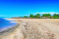 Fila de paraguas de madera en la playa arenosa Fotografía de archivo