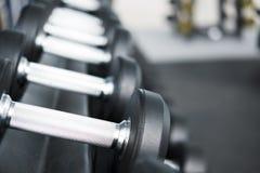 Fila de pesas de gimnasia en gimnasio Pesa de gimnasia negra fijada en el CEN de la aptitud del deporte Fotos de archivo