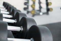 Fila de pesas de gimnasia en gimnasio Pesa de gimnasia negra fijada en el CEN de la aptitud del deporte Fotos de archivo libres de regalías