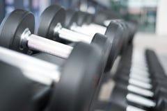 Fila de pesas de gimnasia en gimnasio Pesa de gimnasia negra fijada en el CEN de la aptitud del deporte Imagenes de archivo