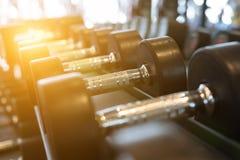 Fila de pesas de gimnasia en gimnasio Pesa de gimnasia negra fijada en el CEN de la aptitud del deporte Foto de archivo