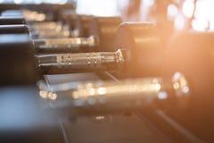 Fila de pesas de gimnasia en gimnasio Pesa de gimnasia negra fijada en el CEN de la aptitud del deporte Fotografía de archivo