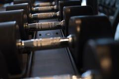 Fila de pesas de gimnasia en gimnasio Pesa de gimnasia negra fijada en el CEN de la aptitud del deporte Foto de archivo libre de regalías