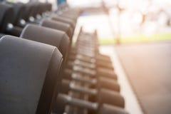 Fila de pesas de gimnasia en gimnasio Pesa de gimnasia negra fijada en el CEN de la aptitud del deporte Imágenes de archivo libres de regalías